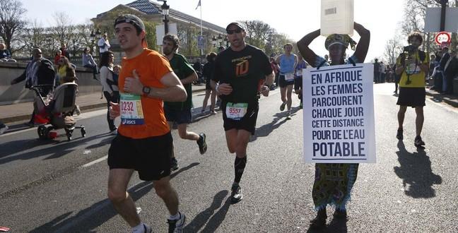 Une Gambienne prend le départ du marathon de Paris en marchant, un bidon d'eau sur la tête